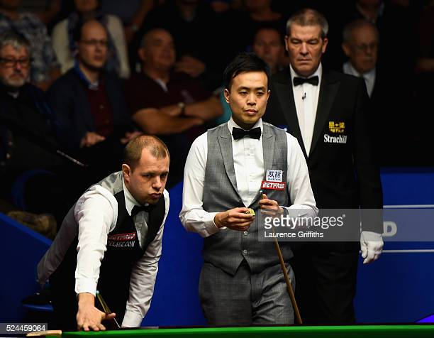 Marco Fu from Hong Kong looks on during his quarter final match against Barry Hawkins of England on day eleven of the World Championship Snooker at...
