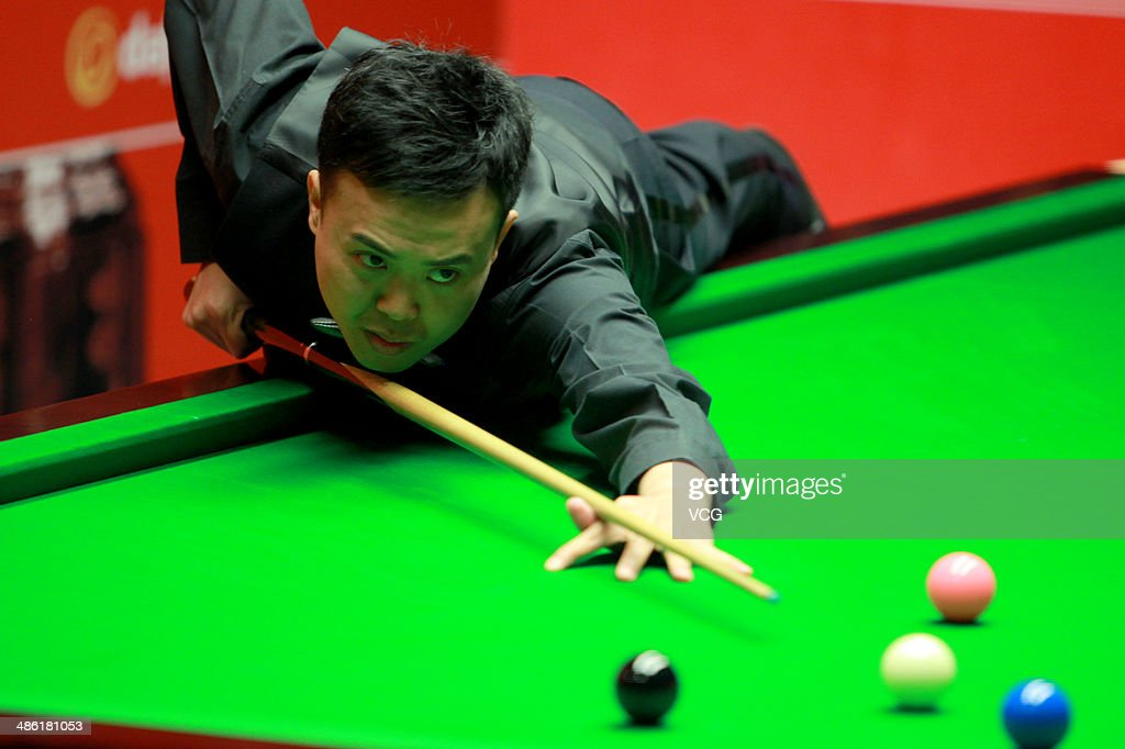 Marco Fu of China plays a shoot against Martin Gould of England during day four of the The Dafabet World Snooker Championship at Crucible Theatre on April 22, 2014 in Sheffield, England.