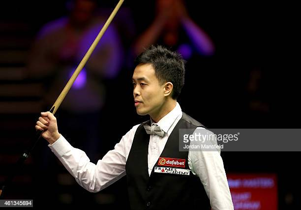 Marco Fu of Hong Kong celebrates making a 147 break during his first round match against Stuart Bingham of England on day one of the 2015 Dafabet...