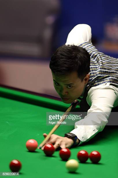 Marco Fu of Hong Kong in action during his semi final match against Mark Selby of England on day fourteen of the World Championship Snooker at...