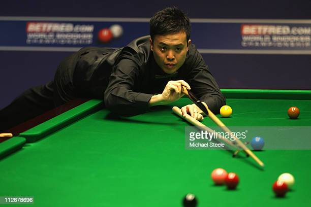 Marco Fu of Hong Kong in action during the round one game against Martin Gould of England on day five of the Betfredcom World Snooker Championship at...