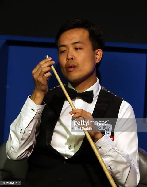 Marco Fu of Hong Kong inspects his cue after the tip fell off during his semi final match against Mark Selby of England on day fourteen of the World...