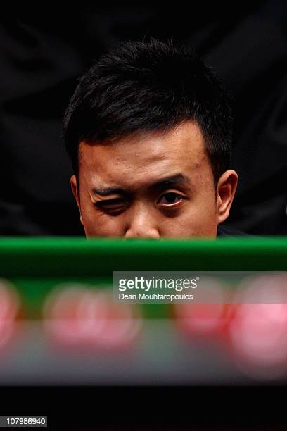 Marco Fu of Hong Kong lines up his next shot in his match against Stephen Maguire of Scotland in Round One of The Ladbrokesmobile Masters on Day 3 at...