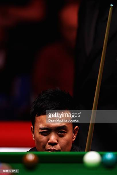 Marco Fu of Hong Kong looks for his next shot against Ding Junhui of China in the Final of The Ladbrokesmobile Masters on Day 8 at Wembley Arena on...