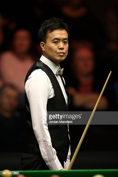 Marco Fu of Hong Kong looks on during his first round match against Stuart Bingham of England on day one of the 2015 Dafabet Masters at Alexandra...