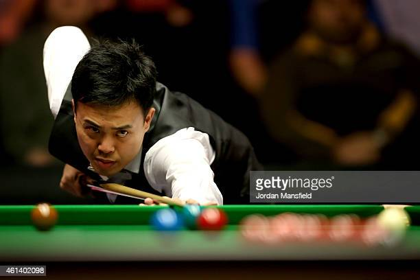 Marco Fu of Hong Kong plays a shot during his first round match against Stuart Bingham of England on day one of the 2015 Dafabet Masters at Alexandra...