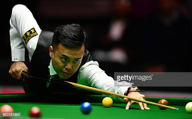 Marco Fu of Hong Kong plays a shot during his semi final match against Ronnie O'Sullivan of England on day seven of the Dafabet Masters at Alexandra...