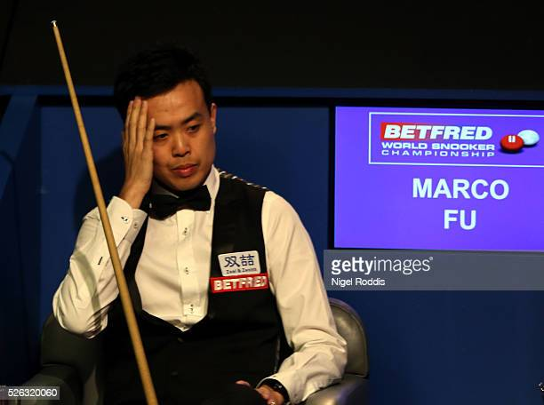 Marco Fu of Hong Kong reacts during his semi final match against Mark Selby of England on day fifteen of the World Championship Snooker at Crucible...