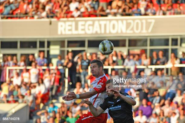 Marco Gruettner of Jahn Regensburg jumps for the ball with Felix Weber of 1860 Muenchen during the Second Bundesliga Playoff first leg match between...