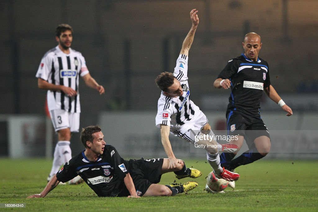 Marco Haller of Aalen (C) is challenged by Zafer Yelen (R) and Manuel Konrad of Frankfurt (L) during the Second Bundesliga match between FSV Frankfurt and VfR Aalen at Frankfurter Volksbank Stadium on March 8, 2013 in Frankfurt am Main, Germany.