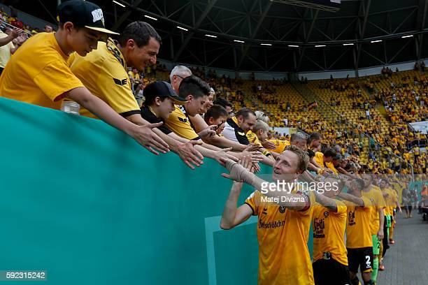 Marco Hartmann of Dresden greets fans with his team mates after the DFB Cup match between Dynamo Dresden and RB Leipzig at DDVStadion on August 20...
