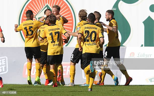 Marco Hartmann of Dresden jubilates with team mates after scoring the first goal during the third league match between FC Hansa Rostock and SG Dynamo...