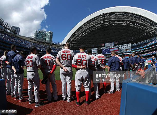 Marco Hernandez of the Boston Red Sox and Henry Owens and Mookie Betts and Jackie Bradley Jr #25 and teammates stand for the playing of the American...