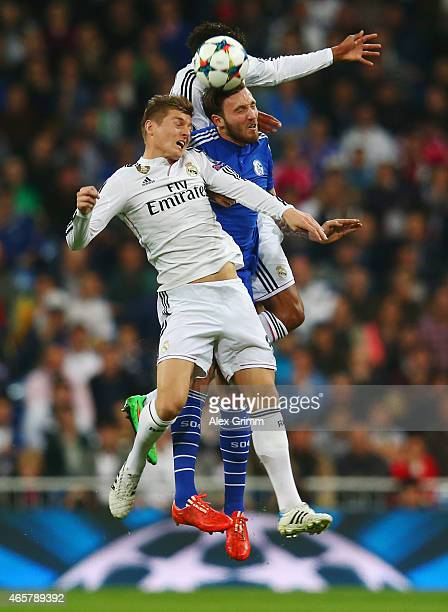 Marco Hoeger of Schalke jumps between Raphael Varane and Toni Kroos of Real Madrid CF during the UEFA Champions League Round of 16 second leg match...