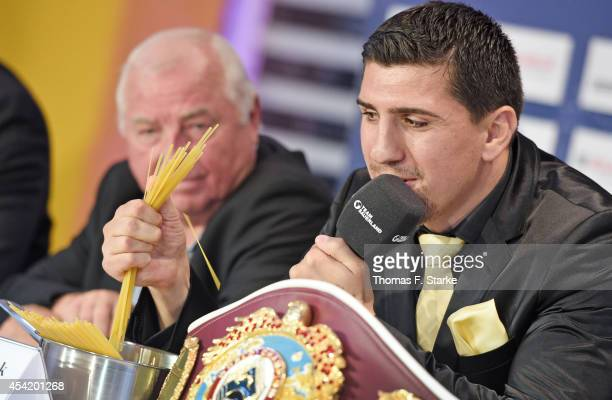 Marco Huck crushes spaghetti while his coach Ulli Wegner looks on during the press conference at Lenkwerk on August 26 2014 in Bielefeld Germany The...
