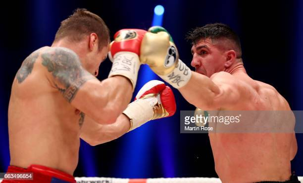 Marco Huck of Germany and Mairis Briedis of Latvia exchange punches during their WBC Cruiserweight World Championship title fight at Westfalenhalle...