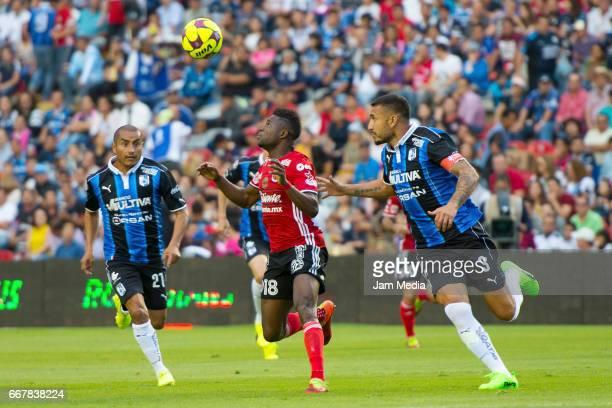 Marco Jimenez of Queretaro Aviles Hurtado of Tijuana and Miguel Martinez of Queretaro look at the ball during the 10th round match between Queretaro...