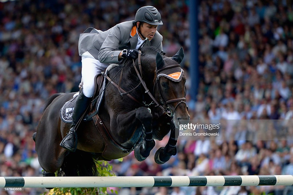 <a gi-track='captionPersonalityLinkClicked' href=/galleries/search?phrase=Marco+Kutscher&family=editorial&specificpeople=2272349 ng-click='$event.stopPropagation()'>Marco Kutscher</a> of Germany and his horse Satisfaction FRH compete in the RWE Prize of North-Rhine-Westphalia jumping competition during day four of the 2012 CHIO Aachen tournament on July 6, 2012 in Aachen, Germany.