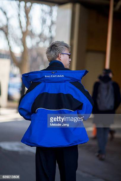 Marco Lau wears a blue Balenciaga by Demna Gvasalia jacket off his shoulders over a blazer and loose Wooyoungmi pants during Milan Men's Fashion Week...