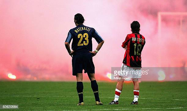 Marco Materazzi of Inter Milan and Rui Costa of AC Milan look on as Inter fans shower the pitch with flares during the UEFA Champions League...