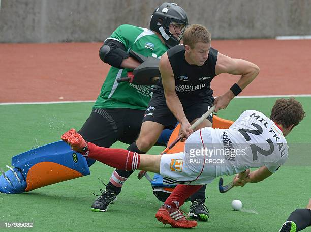 Marco Miltkau of Germany hits the ball past New Zealand Captain Dean Couzins and Hamish McGregor to score during their match at the men's Hockey...