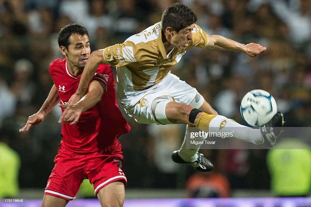 Marco Palacios of Pumas fights for the ball with Pablo Velazquez of Toluca during a match between Toluca and Pumas as part of the Torneo Apertura 2013 Liga MX at Nemesio Siez stadium, on July 31, 2013 in Toluca, Mexico.