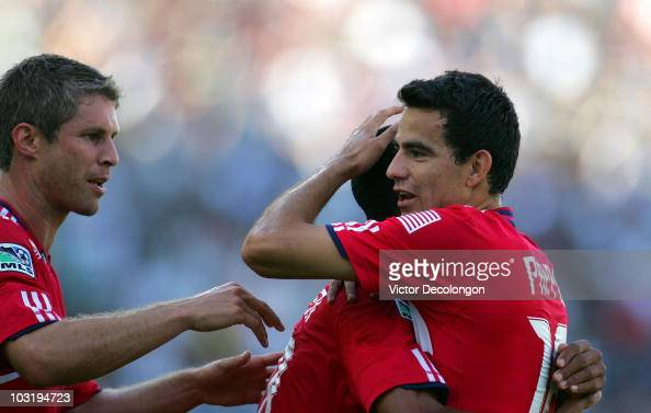 Marco Pappa of the Chicago Fire hugs teammate Mike Banner as teammate Logan Pause looks on after Banner scored in the first half against the Los...