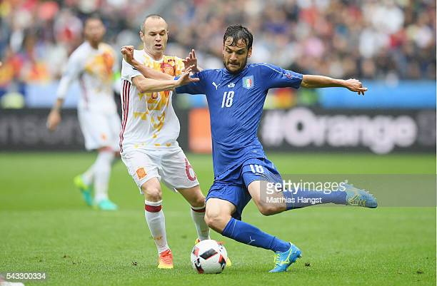 Marco Parolo of Italy and Andres Iniesta of Spain compete for the ball during the UEFA EURO 2016 round of 16 match between Italy and Spain at Stade...