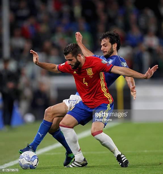 Marco Parolo of Italy competes for the ball with Nacho of Spain during the FIFA 2018 World Cup Qualifier between Italy and Spain at Juventus Stadium...