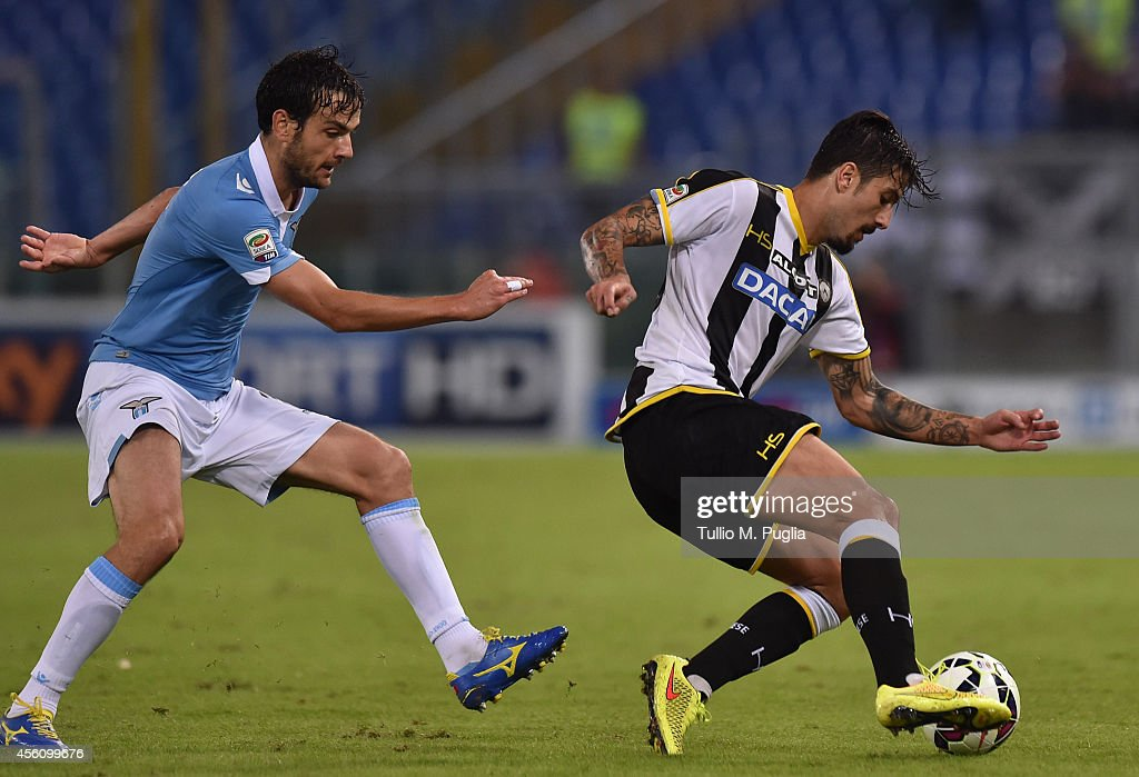 Marco Parolo (R) of Lazio and Panagiotis Kone of Udinese jump for the ball during the Serie A match between SS Lazio and Udinese Calcio at Stadio Olimpico on September 25, 2014 in Rome, Italy.