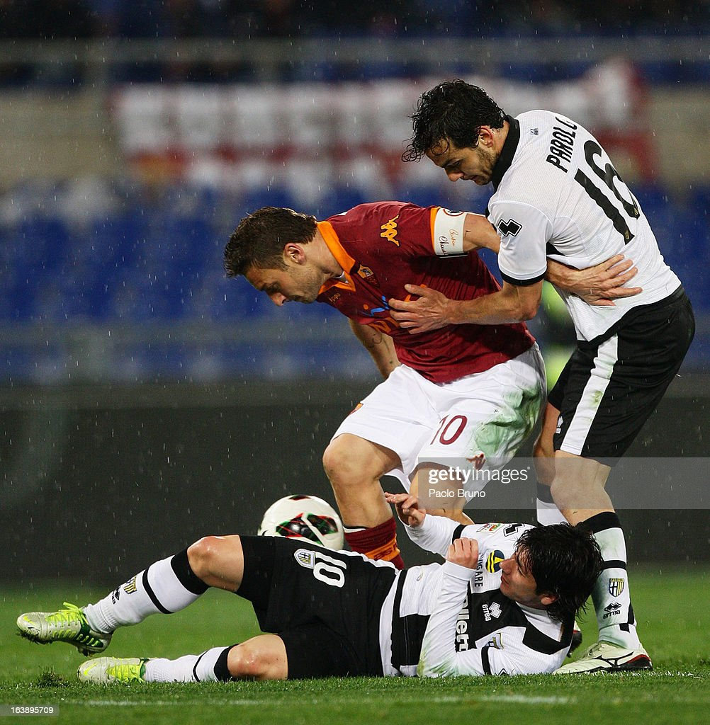 Marco Parolo(R) with Valdes of Parma FC competes for the ball with Francesco Totti (C) of AS Roma during the Serie A match between AS Roma and Parma FC at Stadio Olimpico on March 17, 2013 in Rome, Italy.