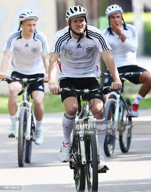 Marco Reus Andre Schuerrle and Mario Goetze ride a bike prior to a Germany training session at their UEFA EURO 2012 training ground on June 10 2012...
