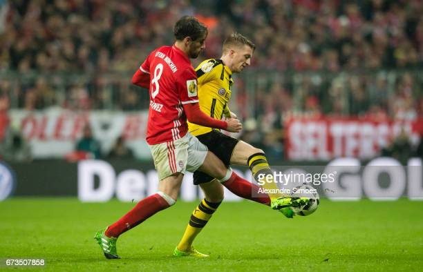 Marco Reus of Borussia Dortmund challenges Javi Martinez of FC Bayern Muenchen during the DFB Cup Semi Final match between FC Bayern Muenchen and...