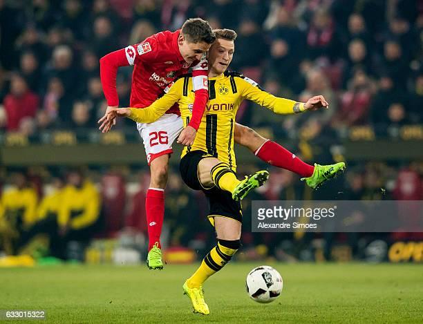 Marco Reus of Borussia Dortmund challenges Niko Bungert of 1 FSV Mainz 05 in an aerial duel during the Bundesliga match between 1 FSV Mainz 05 and...