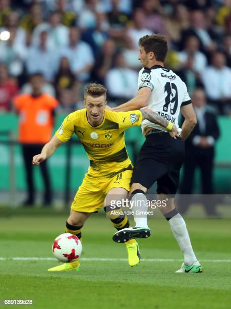 Marco Reus of Borussia Dortmund gets challenged by David Abraham of Eintracht Frankfurt during the DFB Cup Final match between Eintracht Frankfurt...