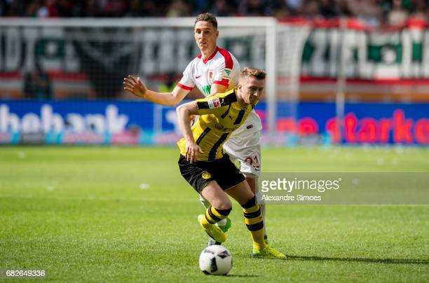 Marco Reus of Borussia Dortmund gets challenged by Dominik Kohr of FC Augsburg during the Bundesliga match between FC Augsburg and Borussia Dortmund...