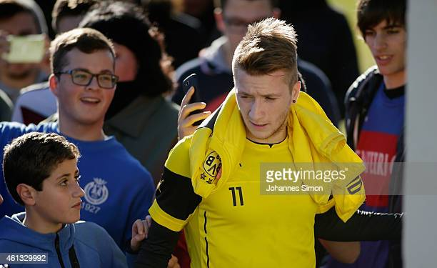 Marco Reus of Borussia Dortmund is surrounded by fans after leaving the pitch during the first training session in the Borussia Dortmund training...