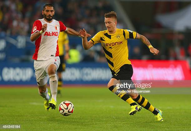 Marco Reus of Borussia Dortmund runs with the ball during the Bundesliga match between FC Augsburg and Borussia Dortmund at SGL Arena on August 29...