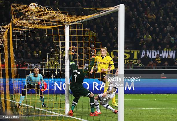 Marco Reus of Borussia Dortmund shoots past Hugo Lloris of Tottenham Hotspur to score their second goal during the UEFA Europa League Round of 16...