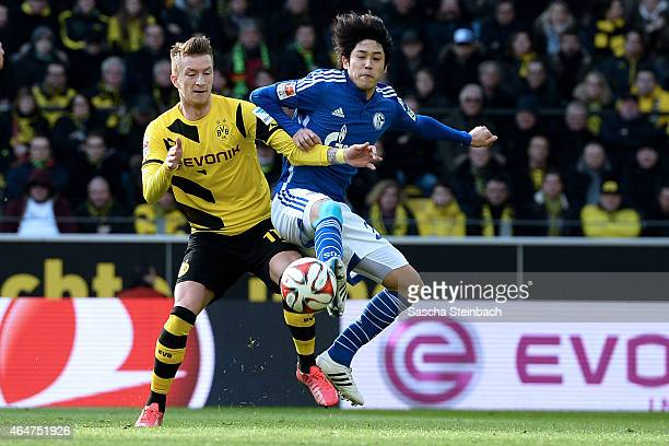 Marco Reus of Dortmund and Atsuto Uchida of Schalke battle for the ball during the Bundesliga match between Borussia Dortmund and FC Schalke 04 at...