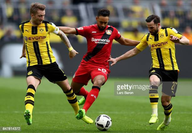Marco Reus of Dortmund and Gonzalo Castro of Dortmund challenge Karim Bellarabi of Bayer Leverkusen during the Bundesliga match between Borussia...