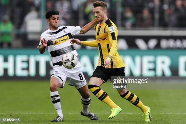 Marco Reus of Dortmund and Mahmoud Dahoud of Moenchengladbach battle for the ball during the Bundesliga match between Borussia Moenchengladbach and...