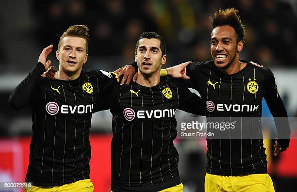 Marco Reus of Dortmund celebrates scoring his goal with Henrikh Mkhitaryan and PierreEmerick Aubameyang during the Bundesliga match between VfL...