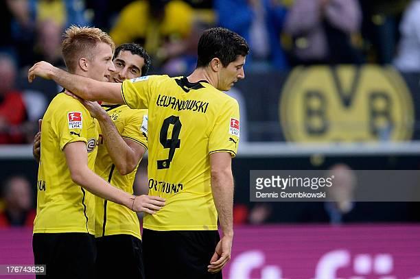 Marco Reus of Dortmund celebrates with teammates Nuri Sahin and Robert Lewandowski after scoring his team's second goal during the Bundesliga match...