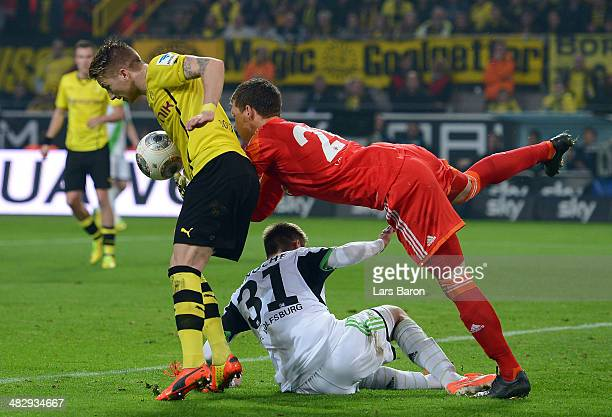 Marco Reus of Dortmund challenges goalkeeper Max Gruen and Robin Knoche of Wolfsburg on his way to score his teams second goal during the Bundesliga...
