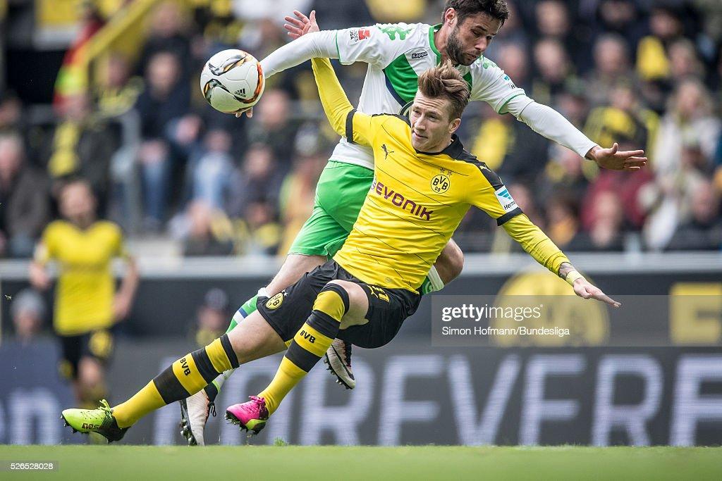 Marco Reus of Dortmund is challenged by Christian Traesch of Wolfsburg during the Bundesliga match between Borussia Dortmund and VfL Wolfsburg at Signal Iduna Park on April 30, 2016 in Dortmund, North Rhine-Westphalia.