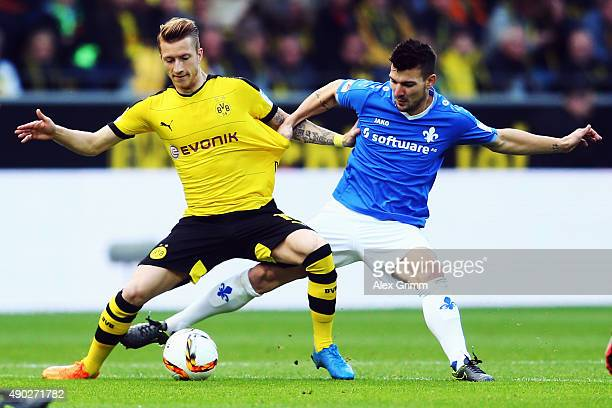 Marco Reus of Dortmund is challenged by Jerome Gondorf of Darmstadt during the Bundesliga match between Borussia Dortmund and SV Darmstadt 98 at...