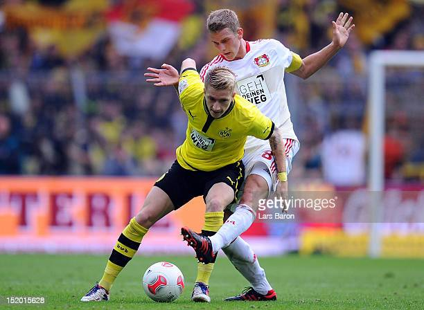 Marco Reus of Dortmund is challenged by Lars Bender of Leverkusen during the Bundesliga match between Borussia Dortmund and Bayer 04 Leverkusen at...
