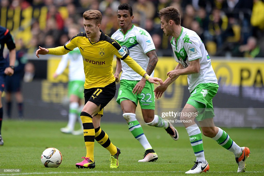 Marco Reus of Dortmund is challenged by Luiz Gustavo and Robin Knoche of Wolfsburg during the Bundesliga match between Borussia Dortmund and VfL Wolfsburg at Signal Iduna Park on April 29, 2016 in Dortmund, Germany.