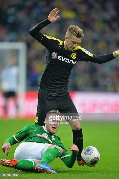 Marco Reus of Dortmund is challenged during the Bundesliga match between Werder Bremen and Borussia Dortmund at Weserstadion on February 8 2014 in...
